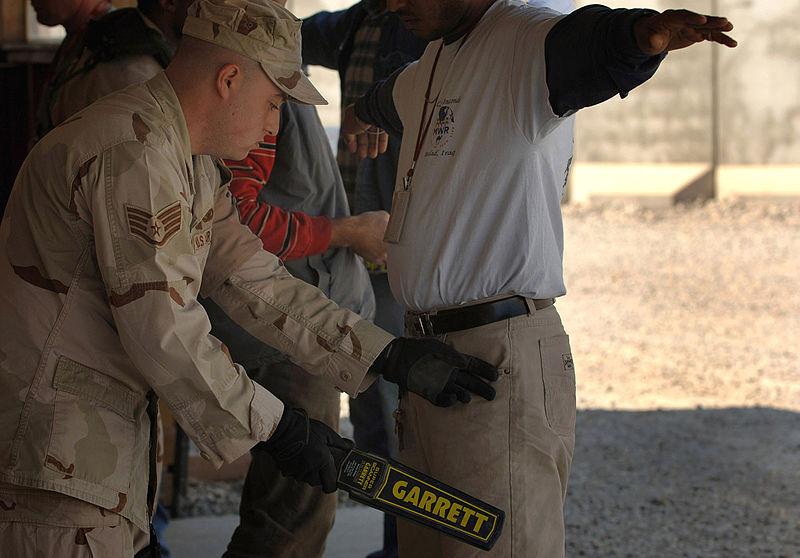 Un soldado está usando un Super Escáner Garret, un detector de metales de mano para buscar armas y contrabando.